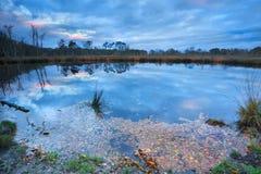 Salida del sol lluviosa del otoño sobre el lago salvaje Fotos de archivo libres de regalías