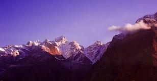 Salida del sol nublada hermosa en las montañas con nieve foto de archivo