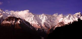 Salida del sol nublada hermosa en las montañas con nieve imagen de archivo