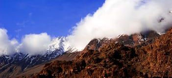 Salida del sol nublada hermosa en las montañas con nieve foto de archivo libre de regalías
