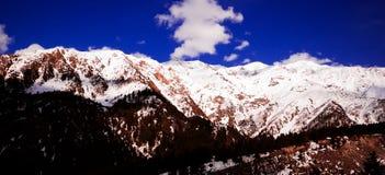 Salida del sol nublada hermosa en las montañas con nieve fotografía de archivo libre de regalías