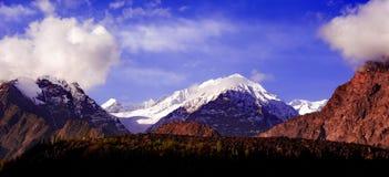 Salida del sol nublada hermosa en las montañas con nieve fotografía de archivo