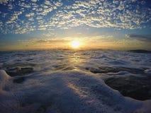 Salida del sol nublada a través del océano Fotografía de archivo libre de regalías