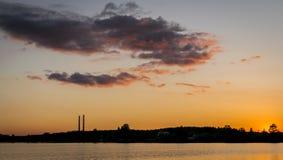 Salida del sol o puesta del sol cerca de un lago con las chimeneas industriales imagenes de archivo