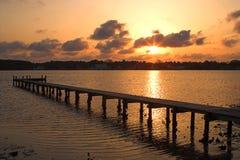 Salida del sol o puesta del sol sobre un embarcadero Imagen de archivo libre de regalías