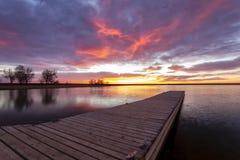 Salida del sol o puesta del sol en el muelle de la pesca con el refle colorido de las nubes Fotos de archivo