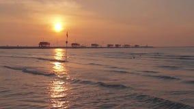 Salida del sol por el mar, delante de la presa con las casas de madera almacen de metraje de vídeo