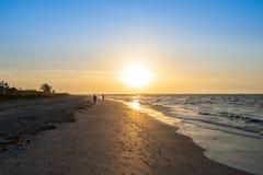 Salida del sol por la playa foto de archivo libre de regalías
