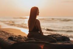 Salida del sol preciosa de la mañana en el mar, silueta de la muchacha en la puesta del sol la mujer se relaja por el mar Concept fotografía de archivo
