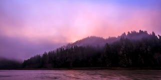 Salida del sol que comienza a consumir la niebla Foto de archivo