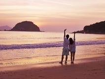 Salida del sol que espera de los pares asiáticos jovenes para en la playa Imagen de archivo libre de regalías