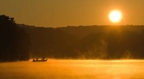 Salida del sol que pesca con caña en un lago Fotografía de archivo