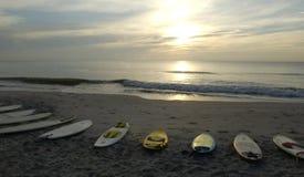 Salida del sol que practica surf Foto de archivo libre de regalías