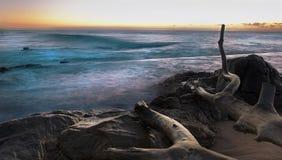 Salida del sol rocosa de la costa con la exposición larga Foto de archivo libre de regalías