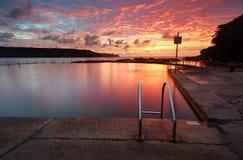 Salida del sol roja del verano sobre la bahía larga de la piscina de la roca del océano de Malabar austral foto de archivo