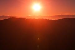 Salida del sol rosácea sobre un horizonte de la montaña imagenes de archivo