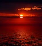 Salida del sol sangrienta sobre el mar Foto de archivo libre de regalías