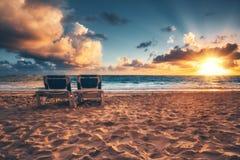 Salida del sol, sillas de playa en la playa del Caribe tropical Imagen de archivo libre de regalías