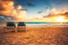 Salida del sol, sillas de playa en la playa carribean tropical Fotos de archivo