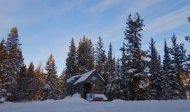 Salida del sol sobre casa minúscula del invierno Imagenes de archivo