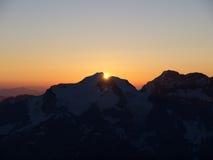 Salida del sol sobre cumbre de la montaña Fotografía de archivo