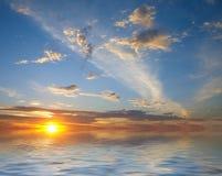 Salida del sol sobre el agua y el cielo Fotografía de archivo libre de regalías