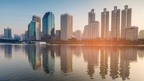 Salida del sol sobre el edificio de la oficina de negocios con la reflexión del agua foto de archivo libre de regalías