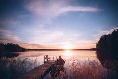 Salida del sol sobre el embarcadero de la pesca en el lago en Finlandia Imagen de archivo