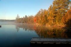 Salida del sol sobre el lago brumoso tranquilo Fotos de archivo libres de regalías