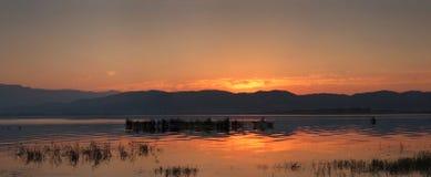 Salida del sol sobre el lago y el pescador Dojran entre las cañas Fotos de archivo