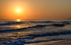 Salida del sol sobre el mar, las ondas de la calma del balanceo, playa arenosa Imágenes de archivo libres de regalías