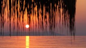 Salida del sol sobre el mar que ve a través un parasol de playa Foto de archivo