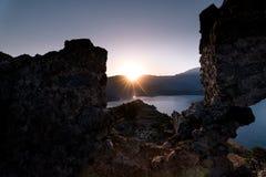 Salida del sol sobre el mar y las montañas Rocas y senery del agua Fotos de archivo