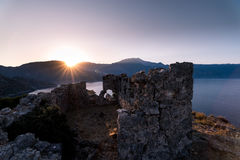 Salida del sol sobre el mar y las montañas Rocas y senery del agua Fotografía de archivo