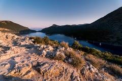 Salida del sol sobre el mar y las montañas Rocas y senery del agua Imagenes de archivo