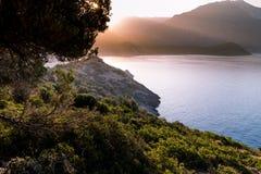 Salida del sol sobre el mar y las montañas Rocas y senery del agua Imagen de archivo