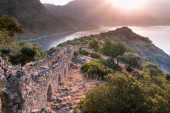 Salida del sol sobre el mar y las montañas Rocas y senery del agua Fotos de archivo libres de regalías