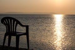 Salida del sol sobre el mar y una silla en la playa Fotos de archivo