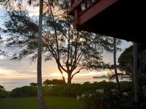 Salida del sol sobre el océano con la casa roja con el balcón imagenes de archivo