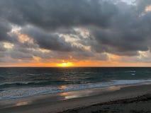 Salida del sol sobre el océano con las nubes oscuras imagenes de archivo