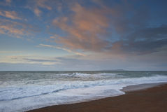 Salida del sol sobre el océano con las nubes rosadas Imágenes de archivo libres de regalías