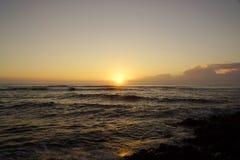 Salida del sol sobre el océano con las ondas que se estrellan a lo largo de orilla Foto de archivo
