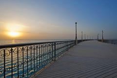 Salida del sol sobre el océano en un embarcadero Imagen de archivo libre de regalías