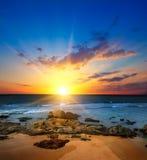Salida del sol sobre el océano y la playa arenosa con los riffs coralinos foto de archivo