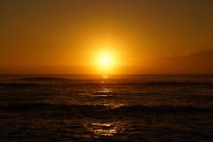 Salida del sol sobre el océano con las ondas que ruedan hacia orilla Imagen de archivo libre de regalías