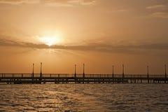Salida del sol sobre el océano en un embarcadero Imágenes de archivo libres de regalías