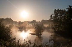 Salida del sol sobre el pantano con niebla Foto de archivo libre de regalías