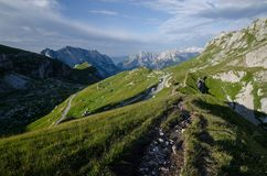 Salida del sol sobre el paso de Mangart con el camino de Mangart en el primero plano, Julian Alps, parque nacional de Triglav, Es fotografía de archivo libre de regalías