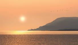 Salida del sol sobre el pueblo de Gaspesia por el mar Imagen de archivo