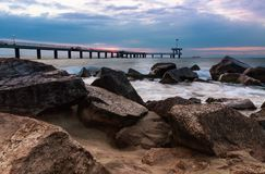Salida del sol sobre el puente en el mar imagenes de archivo